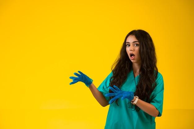 緑の制服を着た若い看護婦と驚いた顔を作るプラスチック手袋
