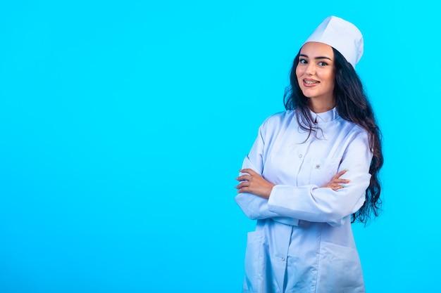 孤立した制服を着た若い看護師は腕と笑顔を閉じます。