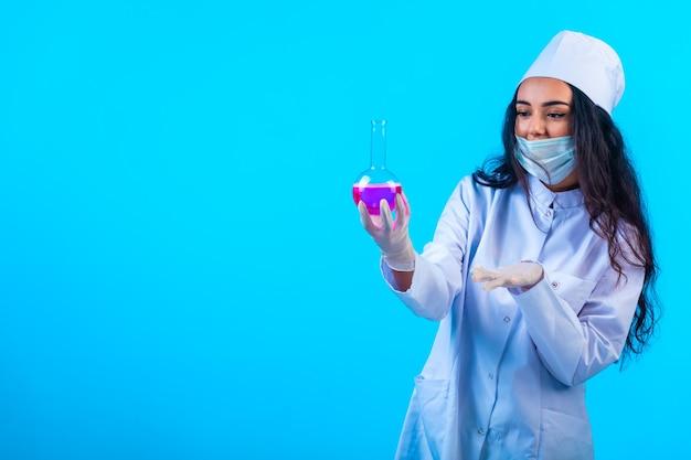 파란색 벽에 테스트 플라스 크를 들고 격리 된 제복을 입은 젊은 간호사.