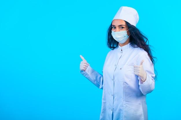 親指を立てる手サインを作る孤立した制服を着た若い看護師。