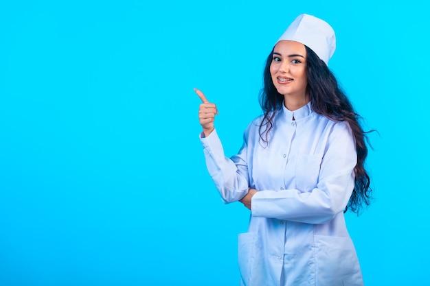 Молодая медсестра в изолированной униформе выглядит веселой и делает положительный знак