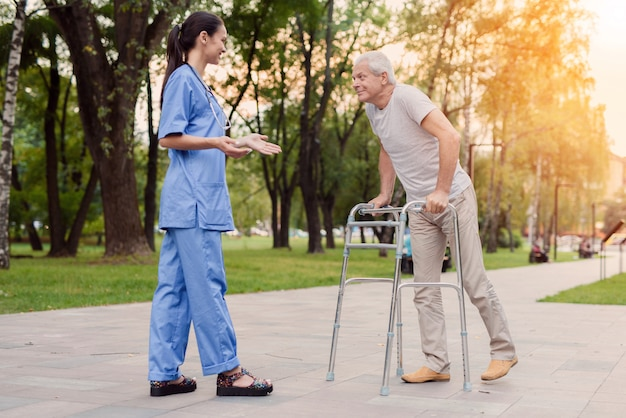 A young nurse is standing in the park and helps elderly man