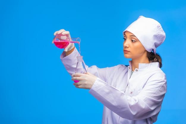 La giovane infermiera fa la reazione chimica in modo professionale.