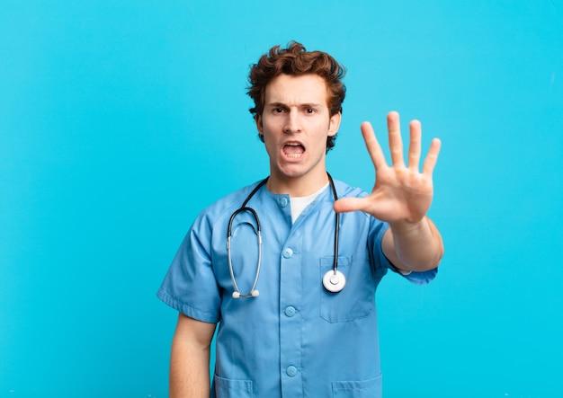 真面目で厳しい、不機嫌で怒っている若い看護婦の男が開いた手のひらを停止ジェスチャーを示し