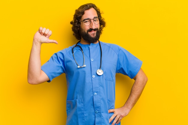 Young nurse man proud pose against yellow background
