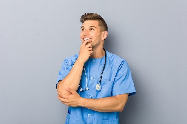 Young nurse man relaxed thinking about something looking at a copy space.