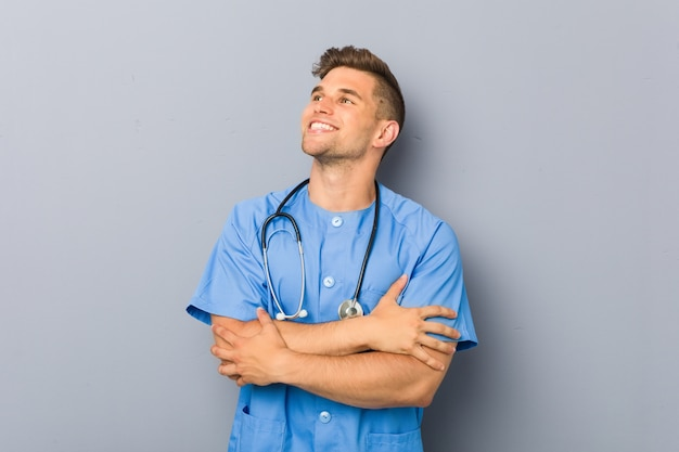 Young nurse man smiling confident with crossed arms.