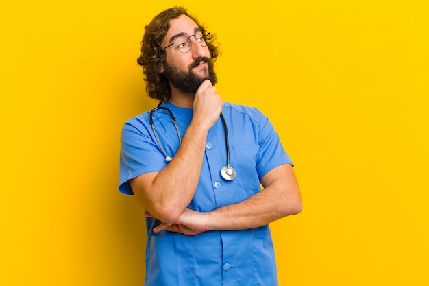 Young nurse man thinking against yellow wall