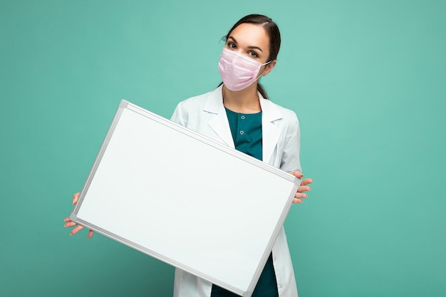 Young nurse in protective face mask and white medical coat holding an empty magnetic board isolated on blue background