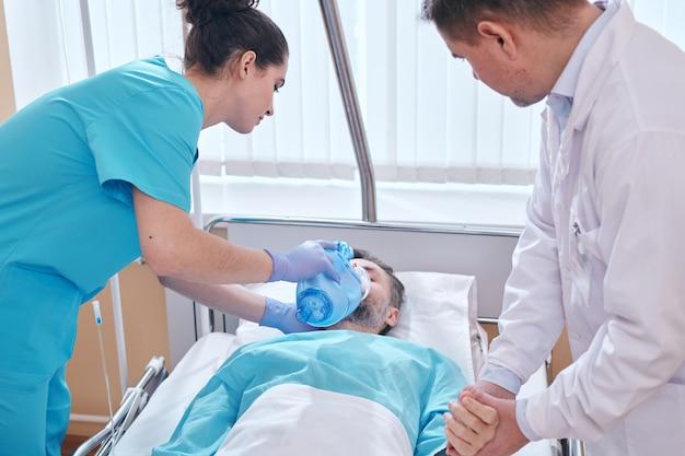Молодая медсестра надевает кислородную маску клапана мешка на лицо пациента и врач проверяет его пульс, пока они оказывают неотложную помощь мужчине