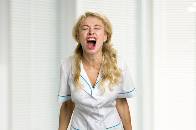 Young nurse screaming in despair. very stressed beautiful young female doctor screaming loudly in frustration with closed eyes.