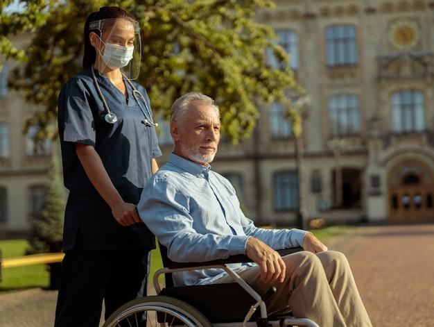 車椅子で成熟した男性患者を押すフェイスシールドとマスクを身に着けている若い看護師