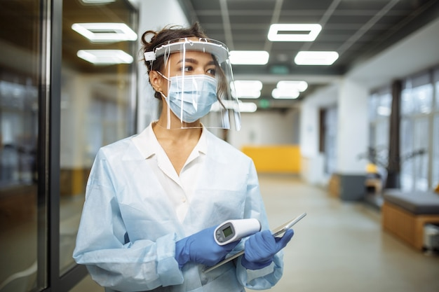 Young nurse wearing medical protective face shield and mask stands at the hospital corridor with a non contact thermometer and tablet ready to test the patients. health care and diagnosis concept.