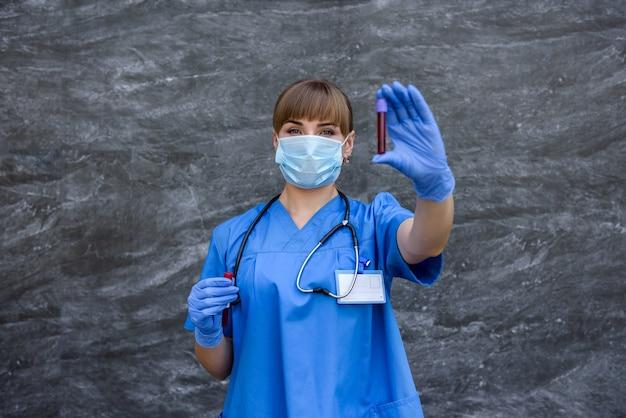 医療用フェイスマスクを持った若い看護師が実験室の血液プローブを指しています。医療の概念。