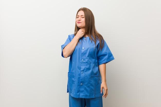 Молодая медсестра у белой стены страдает от боли в горле из-за вируса или инфекции.