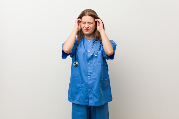 Молодая женщина медсестры против белой стены касаясь висков и имея головную боль.