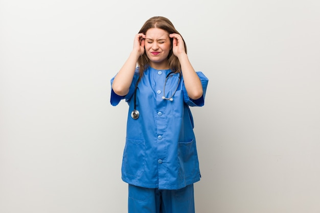 Young nurse woman against a white wall touching temples and having headache.