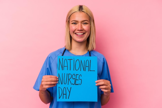 ピンクの壁に分離された国際的な看護師の女性のバナーを保持している若い看護師の女性