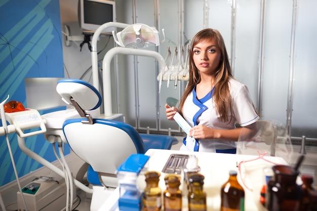 バックグラウンドで機器を備えたクリニックの歯科医院で歯科用椅子の近くに座っている白い制服を着た若い看護婦さん