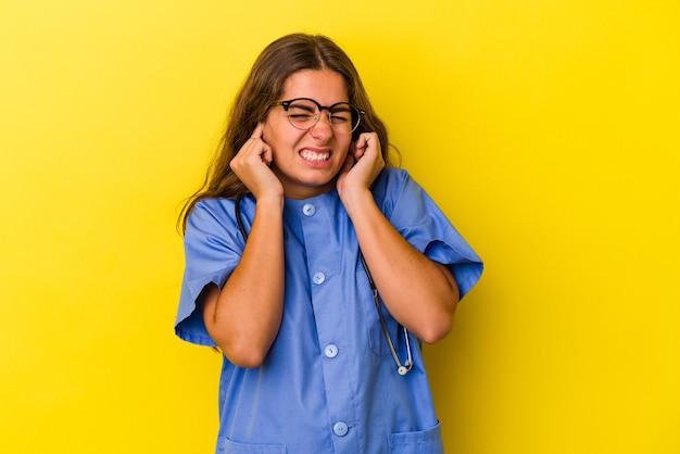 손으로 귀를 덮고 노란색 배경에 고립 된 젊은 간호사 여자.