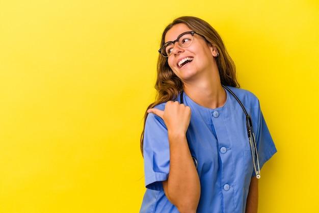 노란색 배경에 격리된 젊은 간호사 여성은 엄지손가락을 치켜들고 웃고 평온합니다.