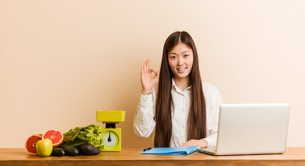 Young nutritionist chinese woman working with her laptop cheerful and confident showing ok gesture