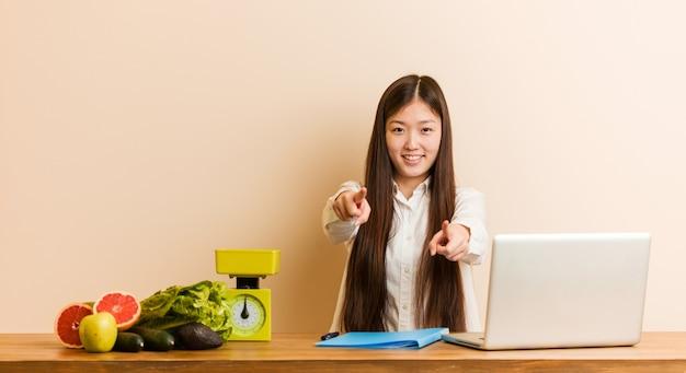 그녀의 노트북을 사용하는 젊은 영양사 중국 여자 앞을 가리키는 밝은 미소.