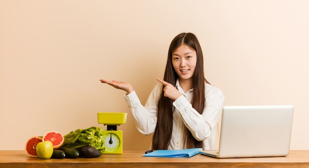 Женщина молодого диетолога китайская работая с ее компьтер-книжкой возбудила держать пустое пространство на ладони.