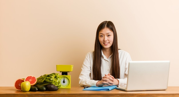 Young nutritionist chinese woman working with her laptop happy, smiling and cheerful.