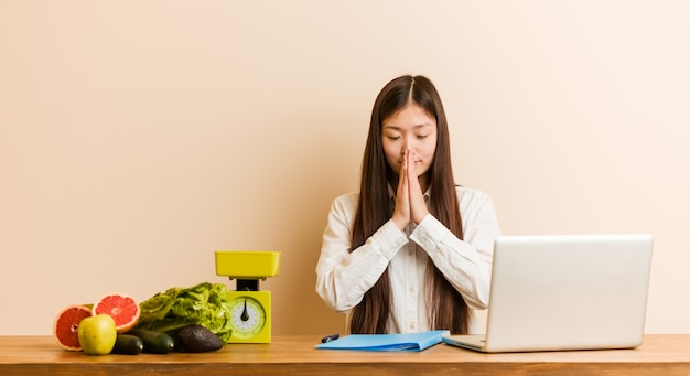 Young nutritionist chinese woman working with her laptop holding hands in pray near mouth, feels confident.