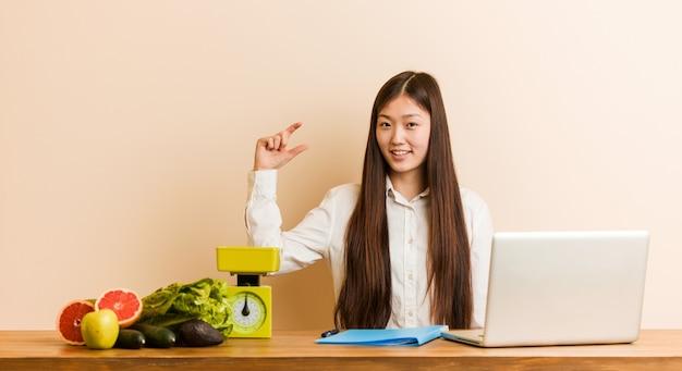 Китайская женщина молодой диетолог, работающая со своим ноутбуком, держит что-то немного указательными пальцами, улыбаясь и уверенно.
