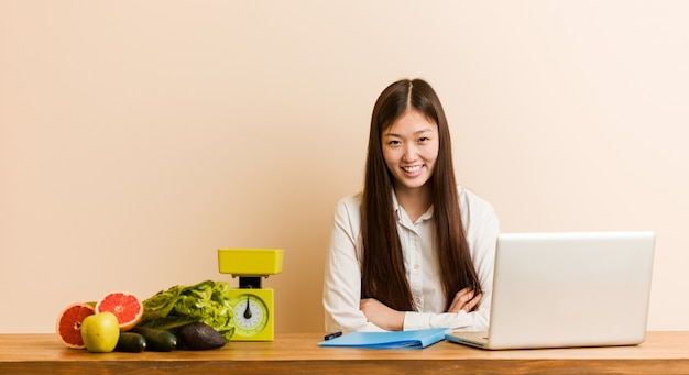 Young nutritionist chinese woman working with her laptop laughing and having fun.