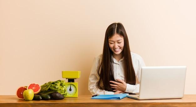 Китайская женщина молодой диетолог, работающая со своим ноутбуком, счастливо смеется и веселится, держа руки на животе.