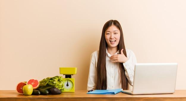 그녀의 노트북을 사용하는 젊은 영양사 중국 여자는 큰 소리로 가슴에 손을 유지 웃음.