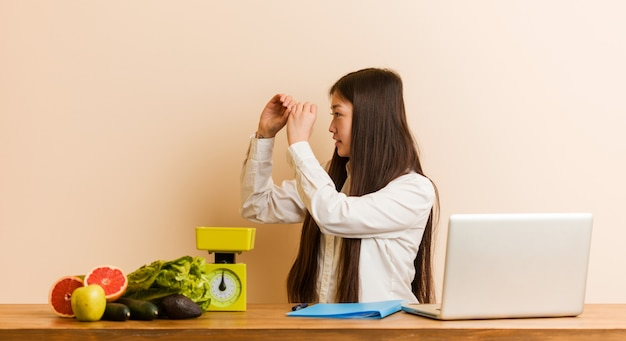 Young nutritionist chinese woman working with her laptop looking far away keeping him hand on forehead.