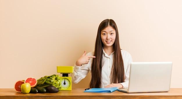 Молодой диетолог китаянка работает со своим ноутбуком, указывая рукой на пространство для копирования рубашки, гордая и уверенная