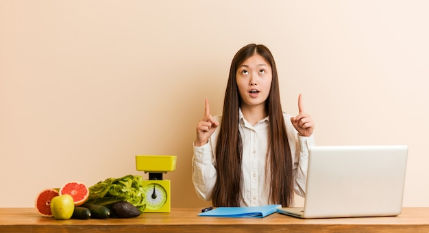 Young nutritionist chinese woman working with her laptop pointing upside with opened mouth.