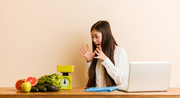 Young nutritionist chinese woman working with her laptop shouts loud, keeps eyes opened and hands tense.