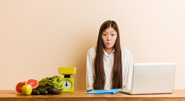 Young nutritionist chinese woman working with her laptop shrugs shoulders and open eyes confused.