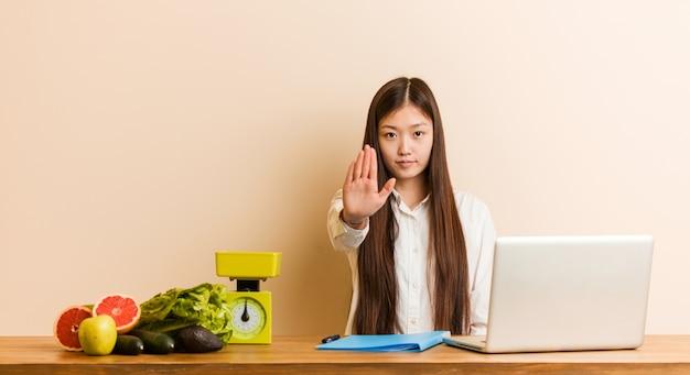 一時停止の標識を示す差し出された手で立っている彼女のラップトップで働く若い栄養士中国女性、あなたを防ぎます。
