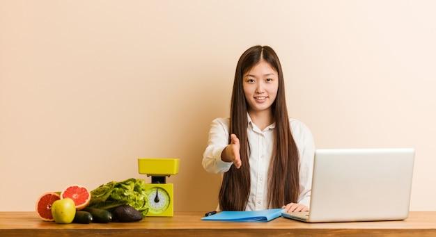 인사말 제스처에 손을 스트레칭 그녀의 노트북을 사용하는 젊은 영양사 중국 여자.