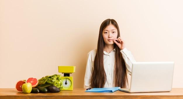 비밀을 유지하는 입술에 손가락으로 그녀의 노트북을 사용하는 젊은 영양사 중국 여자.