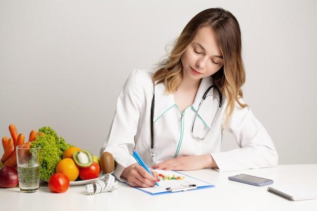 ダイエット計画、健康的な食事を書く若い栄養士の医者。