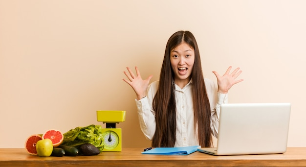 Молодая женщина диетолог работает с ее ноутбуком, празднует победу или успех
