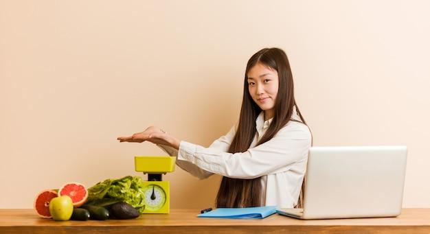 Молодая женщина диетолог работает со своим ноутбуком, держа копией пространства на ладони