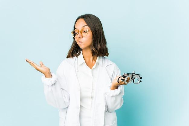 若い眼科医のラテン系女性は、コピースペースを保持するために肩をすくめることに混乱し、疑わしい。