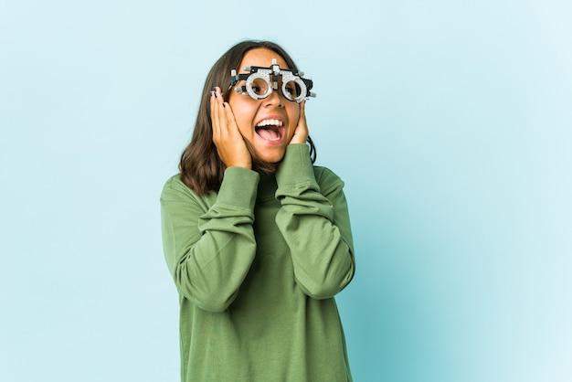 Латинская женщина-окулист закрывает уши руками, пытаясь не слышать слишком громкий звук.