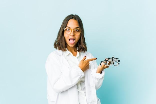 Молодая женщина латинского окулиста возбуждена указывая указательными пальцами прочь.
