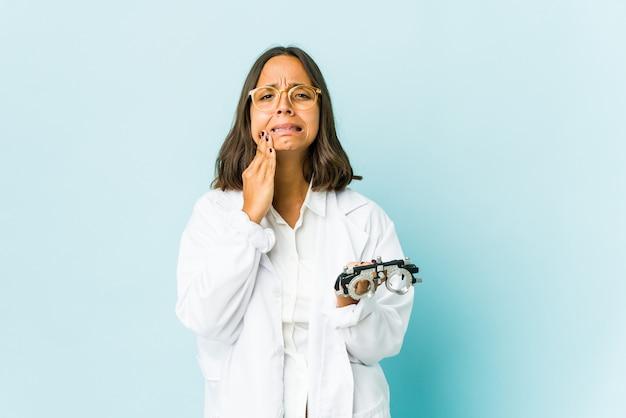 Young oculist latin woman having a strong teeth pain, molar ache.