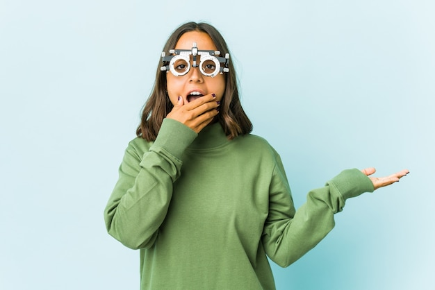 Латинская женщина молодой окулист держит место для копирования на ладони, держит руку над щекой. поражен и обрадован.